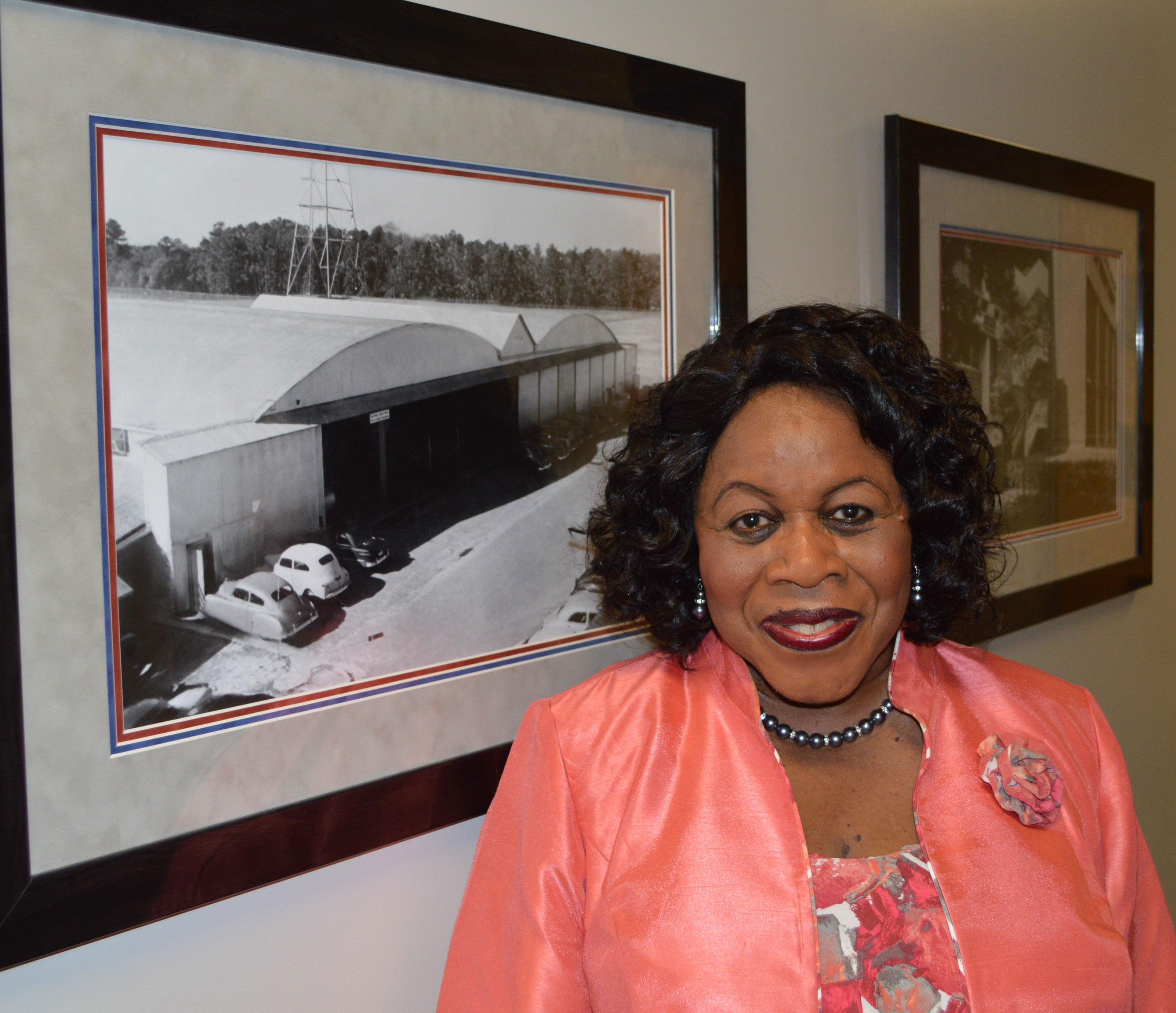 """Shirley Kelly stands in front of a picture of the building she worked in when she started with the College of Engineering in 1967. They called it """"the Hanger."""""""