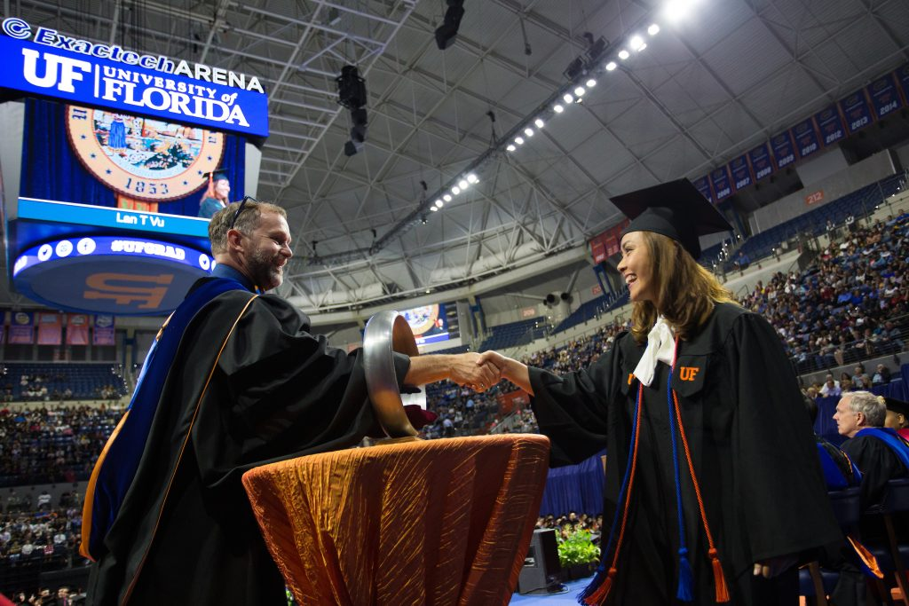 Student shakes hand through Order of the Engineer ring.