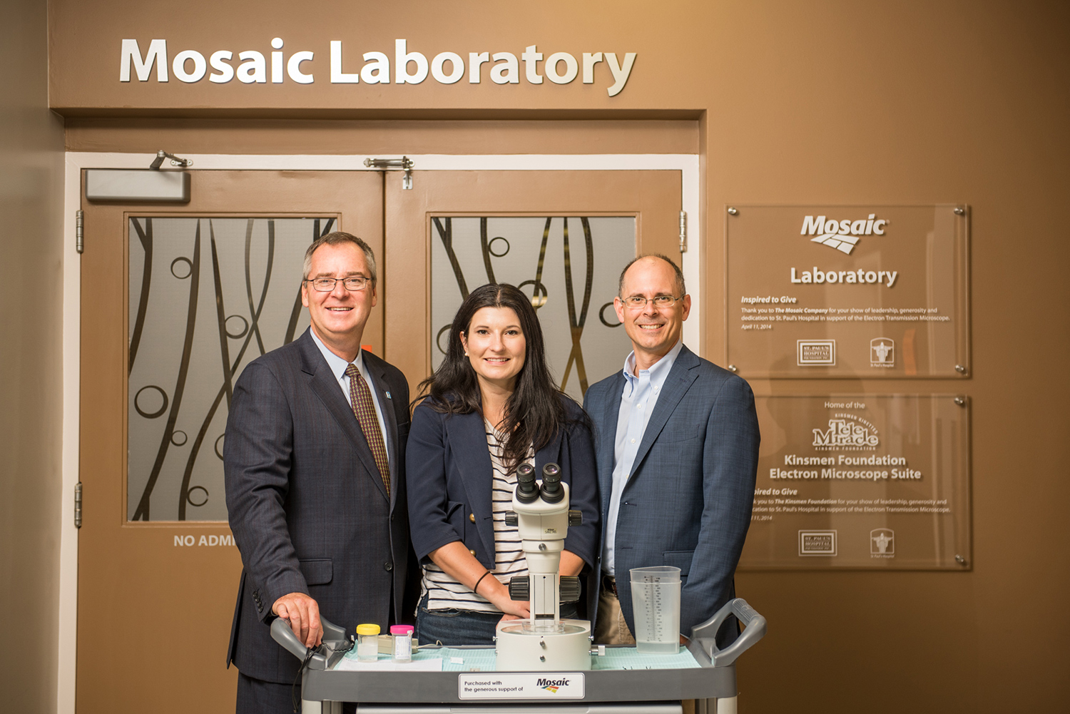 SPH Foundation CEO Bruce Acton with Mosaic Senior Director of Public Affairs Sarah Fedorchuk and Mosaic Senior Vice President Bruce Bodine at the entrance to the Mosaic Laboratory at St. Paul's Hospital (Saskatoon, Saskatchewan), which was funded by the company's philanthropy.