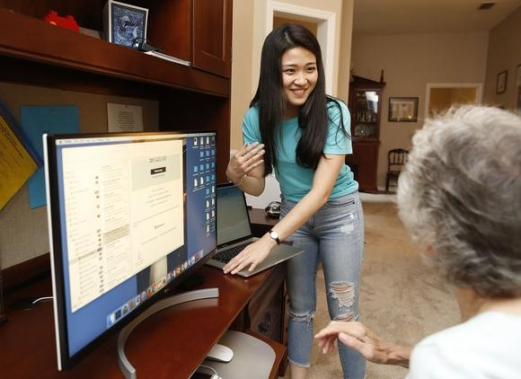Ming Yang helps a senior citizen with her computer.