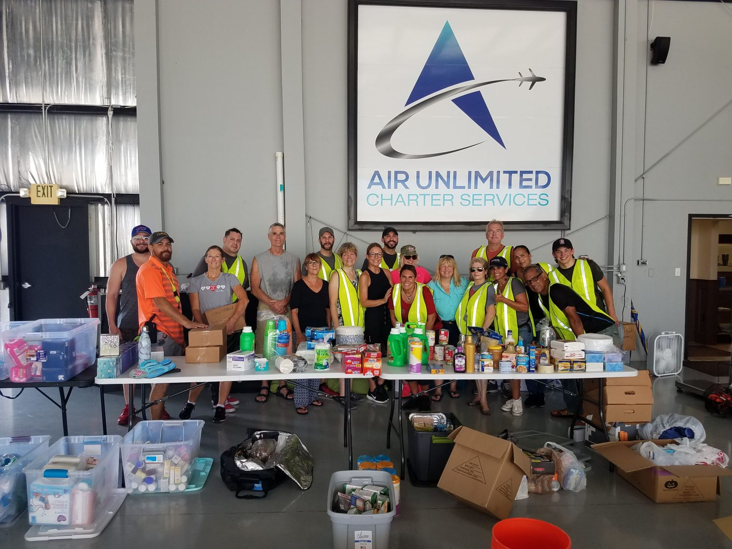 Volunteers behind a table of donated items at Air Unlimited warehouse.