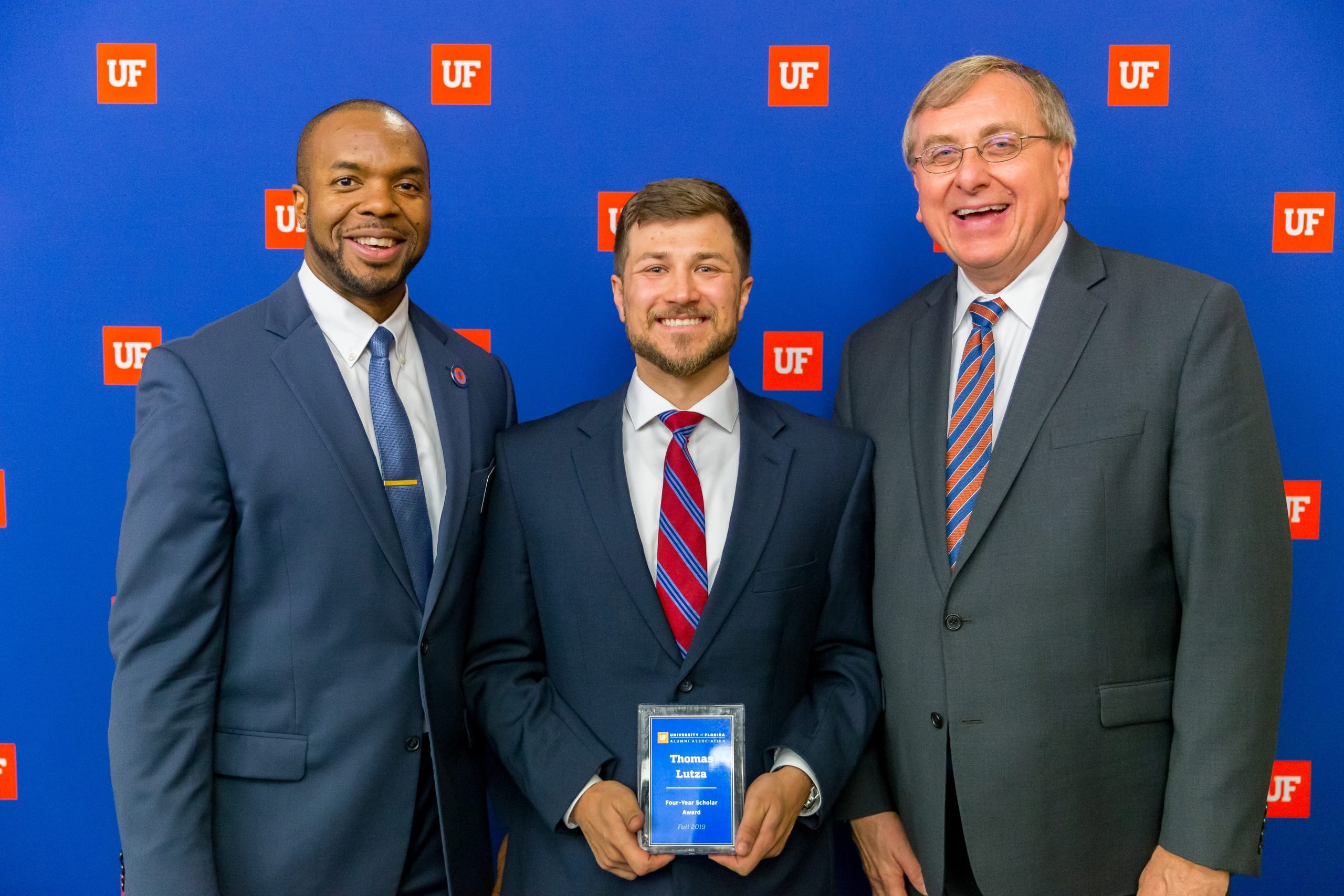 Curtis Taylor, Ph.D and President Fuchs with Thomas Lutza holding award